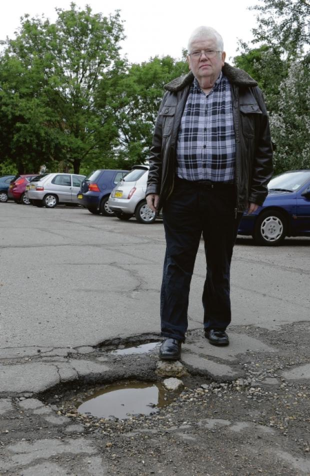 Basildon Recorder: Councillor Phil Rackley by one of the deep potholes in the car park at the Laindon Centre