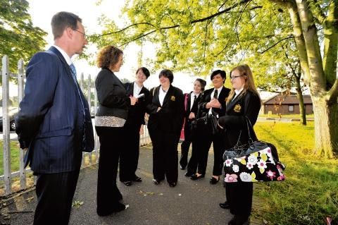 Checking in – headteacher Dr Rory Fox and associate vice principal Sheren Breslin meet pupils outside the academies