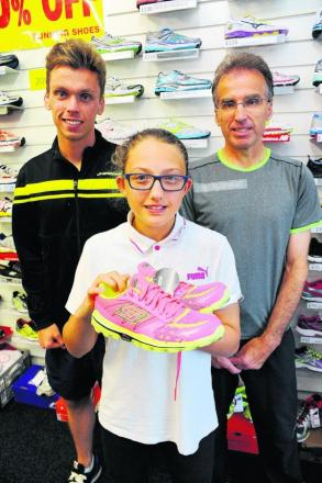 Connie picks up her prize - a pair of Skechers trainers - from Paul and Mike Whittaker at Runner's Edge